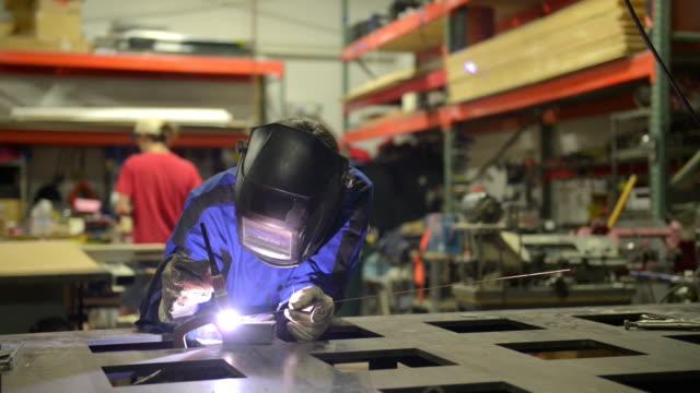 Welder working on metal - DOLLY SHOT