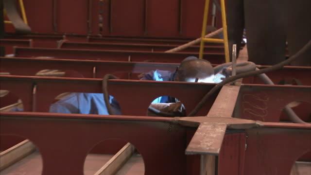 welders work on a large, steel beam. - welding stock videos & royalty-free footage