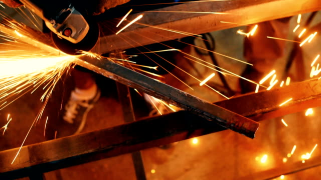 Welding and grinding metal at a factory.