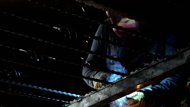 welding metal, unrecognizable worker with protective helmet welding metal in workshop. - welding helmet stock videos & royalty-free footage