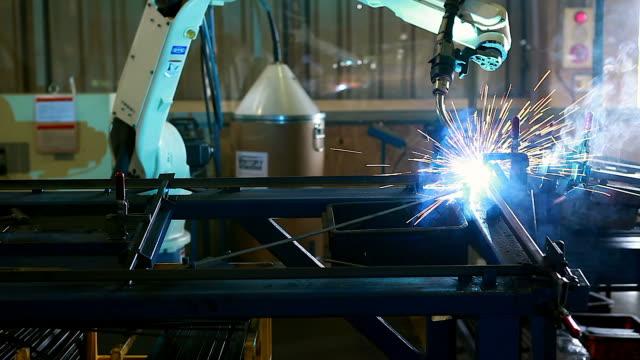 Schweißroboter repräsentieren die Bewegung. In der Kfz-Teile-Industrie.