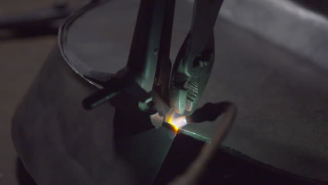 Welding seams of two pieces of sheet metal held with a clamp and pliers