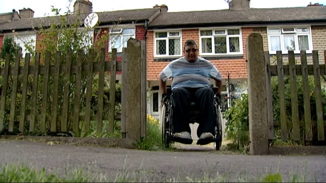 new disability benefit system extended; northamptonshire: corby: lotun from house in wheelchair lotun away along road in wheelchair - northamptonshire stock-videos und b-roll-filmmaterial
