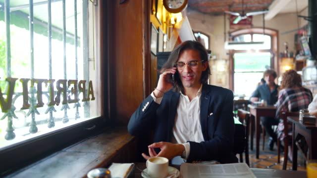 gut gekleideter geschäftsmann, der auf dem smartphone spricht und kaffee im café trinkt - langes haar stock-videos und b-roll-filmmaterial
