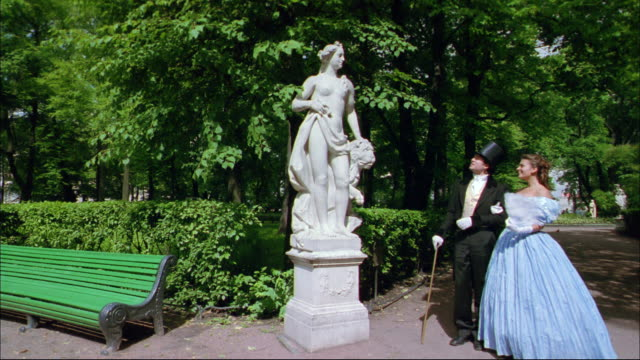 A well dressed couple admires a statue before sitting down on a park bench.