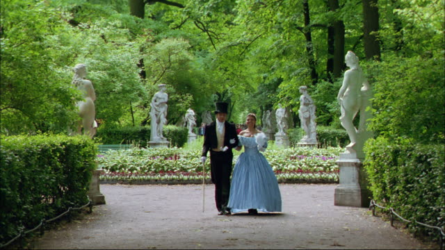 A well dressed couple walks through a beautiful garden.