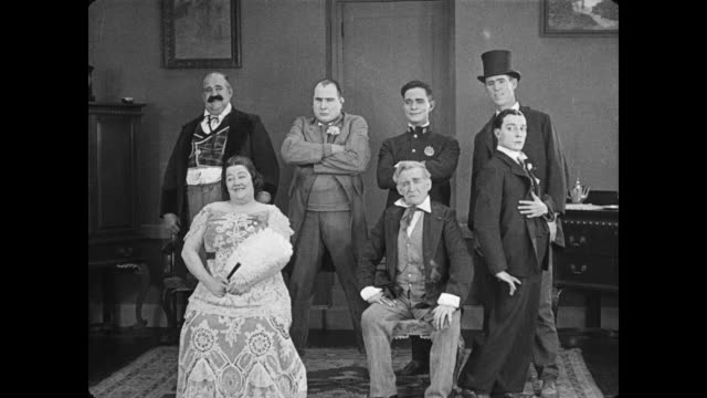 1922 well dressed family pose awkwardly with man (buster keaton) for group photo as camera slides off tripod and flash scares everyone - fotografiska teman bildbanksvideor och videomaterial från bakom kulisserna