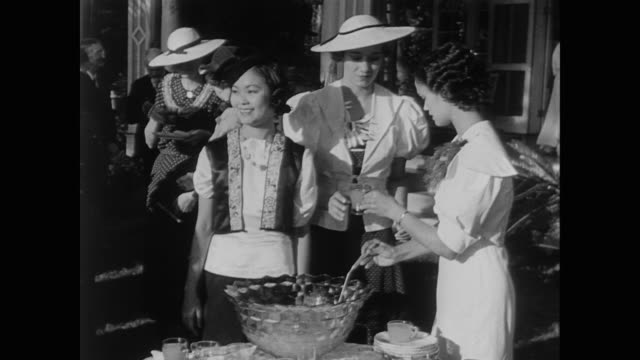 well dressed japanese and anglo men and women help themselves to punch at formal gathering in the us during wwii - guerra del pacifico video stock e b–roll