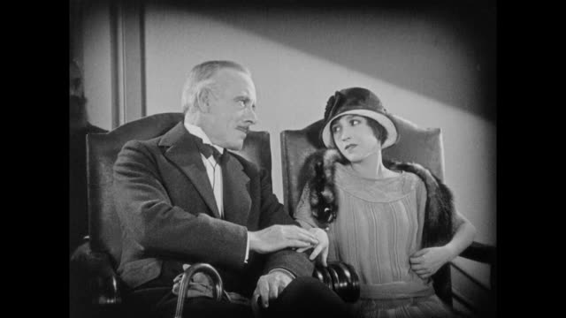 1925 well dressed man and woman sit uncomfortably in high backed chairs - 無声映画点の映像素材/bロール