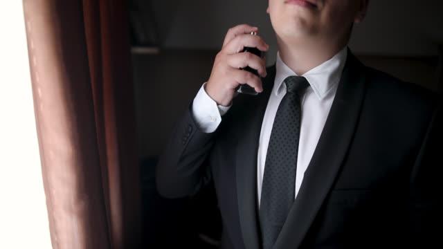 vídeos de stock e filmes b-roll de well dressed man applying perfume - desodorante