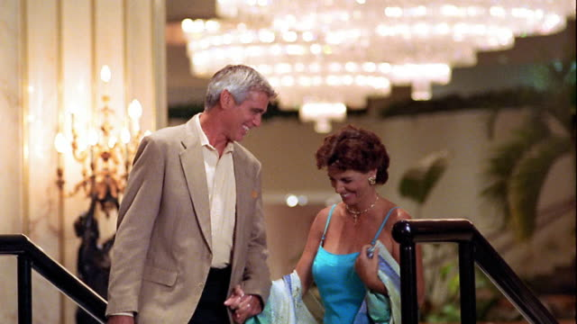 ms well dressed middle age couple walking arm in arm up stairs in ornate lobby, talking + laughing - arm in arm stock videos & royalty-free footage