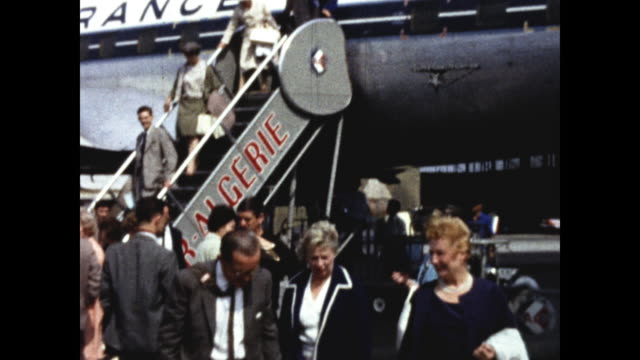 """well dressed people exiting an airplane using a ramp; """"france"""" printed on the plane body; two women and one man carrying bags and luggage talking to... - luggage stock videos & royalty-free footage"""