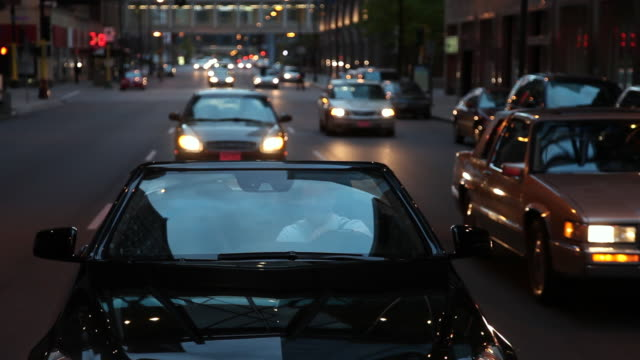 ms well dressed succesful young man driving in modern convertible car through urban area / minneapolis, minnesota, united states - 乗物後部から見た視点点の映像素材/bロール