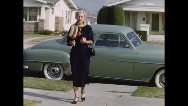 a well dressed woman walks from her 1940's car in palm springs. - 1940~1949年点の映像素材/bロール