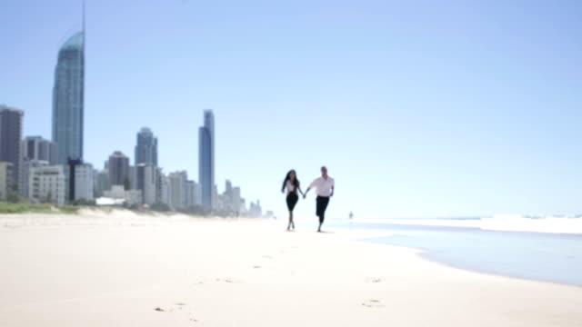 Gut gekleidete junge Paar Laufen am Strand