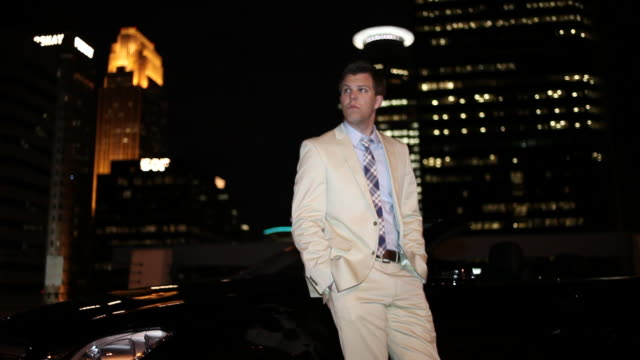 vídeos de stock, filmes e b-roll de ms tu well dressed young man standing next to his modern convertible car with confidence at night in urban area / minneapolis, minnesota, united states - olhando ao redor