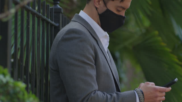 well dressed young man types on his smart phone as he leans aganist a metal fence - formal businesswear stock videos & royalty-free footage