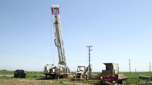 well drilling for groundwater in fresno california on september 23 wide shots of drilling rig being lifted upright from the truck pans up and down of... - groundwater stock videos and b-roll footage