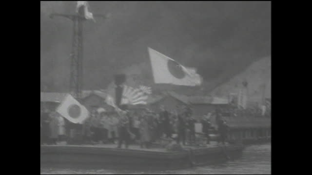 well wishers wave japanese flags as they welcome prisoners of the soviets since ww ii home to maizuru port. - lingua giapponese video stock e b–roll