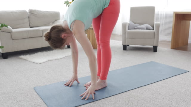 well-built female practicing yoga posture on yoga mat - posture stock videos & royalty-free footage