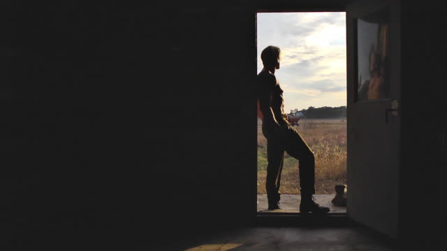 well-built old-time farm hand stands in the doorway of a log cabin and  watches the sun set. - doorway stock videos and b-roll footage