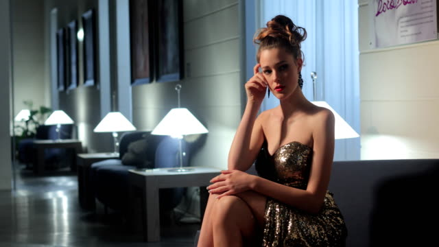 Well-Dressed Beautiful Young Woman Sitting Alone in a Lobby