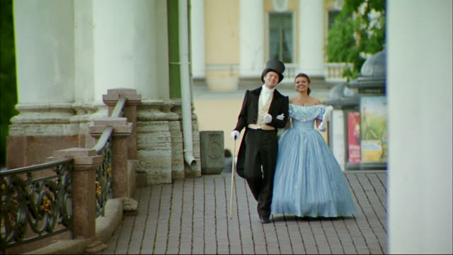 A well-dressed couple walks on the patio of a mansion.
