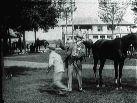 montage well-dressed man leaving store with a wad of cash/ checking out a horse before the race and dropping a note / spectators betting and watching a horse race at a track / united states - anno 1906 video stock e b–roll
