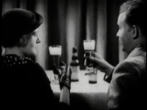 1936 MONTAGE Well-dressed people sipping beer at tables /
