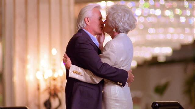 stockvideo's en b-roll-footage met ms profile well-dressed senior couple kissing in ornate lobby area then walking down stairs - 70 79 jaar