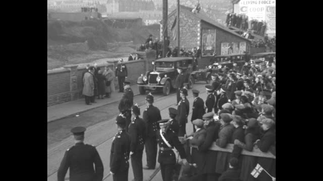 Welsh crowd raises cheers as Edward Prince of Wales decars in Porth greets local officials / Prince and local officials walk past cheering crowds /...