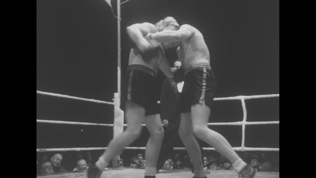 Welsh heavyweight boxer Tommy Farr enters ring walks around ring waving at crowd / Farr goes to corner / CU timekeeper ringing bell to start fight /...