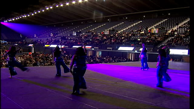 wembley arena re-opens after restoration; wembley arena: int back view of dancers performing on stage in front of audience - arena only half full - wembley arena stock videos & royalty-free footage