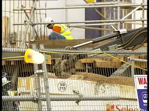 wembley stadium builders announce losses on project; date unknown workers among seats in stadium stadium mechanical digger lifting stones stadium tx... - wembley stock videos & royalty-free footage