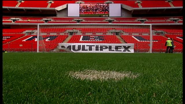 wembley stadium construction nears completion: stadium interior general views; construction worker sitting in empty stands; goal mouth with multiplex... - wembley stadium stock videos & royalty-free footage