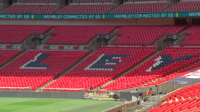London Wembley Wembley Stadium EXT Wembley Stadium GVs / Black writing on red seats / wide shot seats / sprinklers on grass pitch