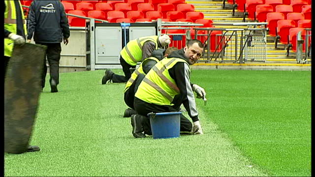 wembley stadium grounds manager prepares for forthcoming finals; england: london: wembley stadium: ext wembley stadium and pitch / lawn movers lined... - グランドキーパー点の映像素材/bロール
