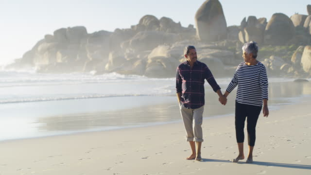 we're choosing to spend our retirement out on the beach - senior couple stock videos & royalty-free footage