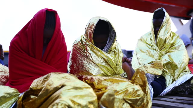 West African women sit wrapped in survival blankets to keep warm on board the Topaz Responder MOAS' 'Migrant Offshore Aid Station's' search and...