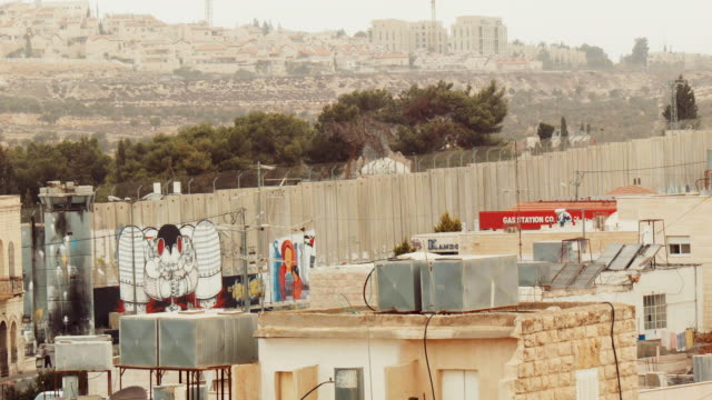 west bank barrier in bethlehem with israeli settlement in background - palestinian territories stock videos and b-roll footage