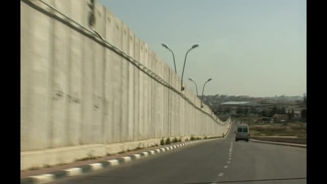 vídeos de stock e filmes b-roll de condoleezza rice meets mahmoud abbas tracking shot from moving car along past wall separation barrier across land man climbing over fence people... - israel