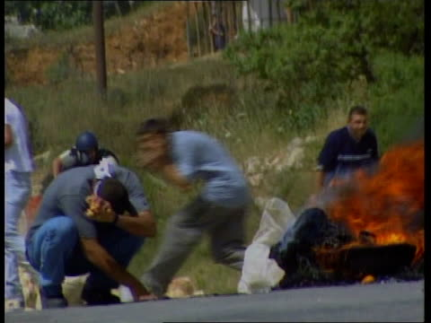 burning barricade in road palestinians gathered in street as man throws stones palestinians in street i/c - boundary stock videos & royalty-free footage