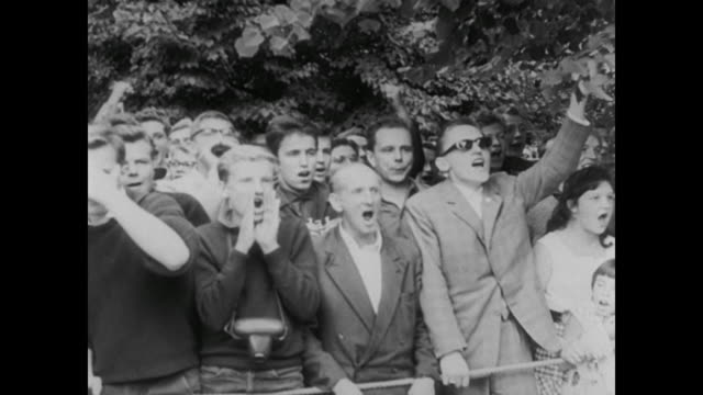 vidéos et rushes de west berliners shout and chant in protest at soldiers guarding the berlin wall - fist