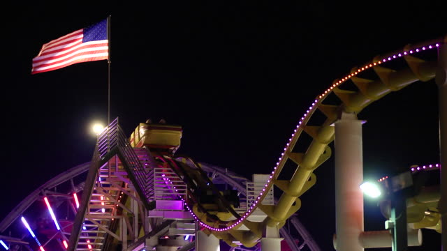 vidéos et rushes de west coaster roller coaster track w/ flashing lights, passenger car approaching, moving slowly down & up hill & out of frame, american flag on top of... - port saïd