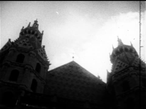 vidéos et rushes de west front of stephansdom w/ two romanesque towers ws people walking out of riesentor roman catholic religion religious archdiocese of vienna seat of... - 1952
