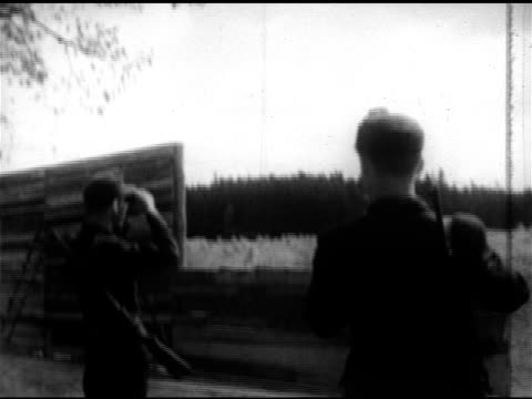 vidéos et rushes de germany west german border guard using binoculars two guards w/ binoculars at border ws people walking out of woods into meadow tu ms people walking... - 1952