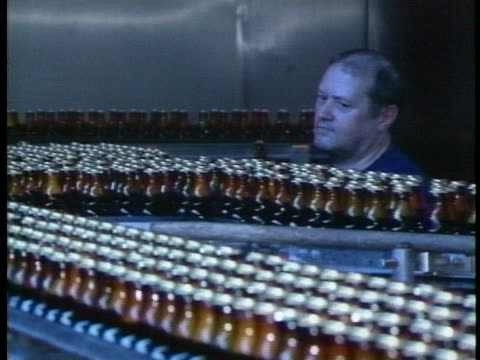 a west german brewery worker watches bottles on a conveyor - healthcare and medicine or illness or food and drink or fitness or exercise or wellbeing stock-videos und b-roll-filmmaterial