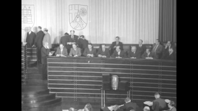 west german bundestag members raise hands in a vote on robert schuman's plan for european economic cooperation / ballots are counted atop tall dais /... - 西ドイツ点の映像素材/bロール