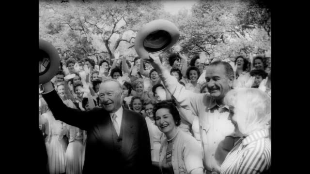 / west german chancellor konrad adenauer arrives by helicopter at stonewall texas with vice president lyndon johnson / a gathered crowd waves flags... - winken stock-videos und b-roll-filmmaterial