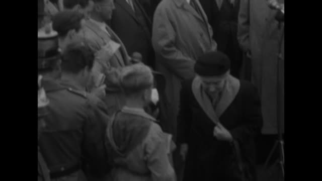 west german chancellor konrad adenauer walks waves from sizable group of men in overcoats / cameramen / old woman stands after kissing adenauer's... - 1955 stock-videos und b-roll-filmmaterial